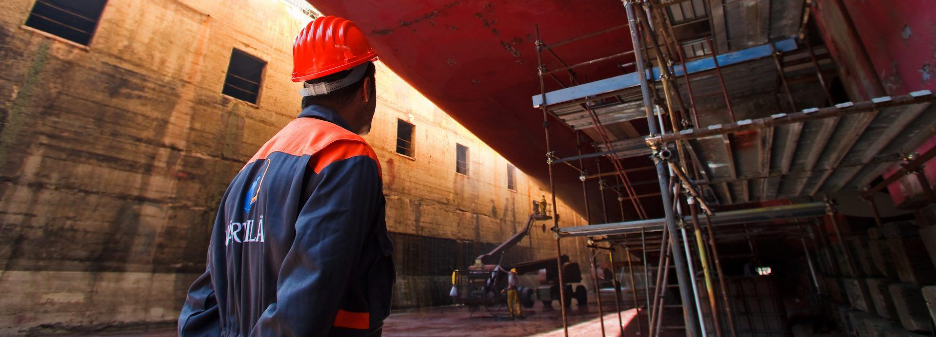Worker with ship in dry dock
